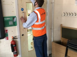 Tradesman working on fire door installed by Aran Fire ProtectionTradesman working on fire door installed by Aran Fire Protection